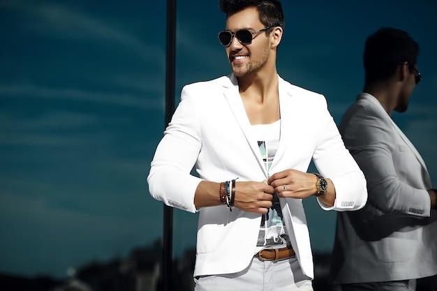 Retrato da moda do homem jovem bonito modelo sexy empresário casual pano terno em óculos de sol na rua Foto gratuita