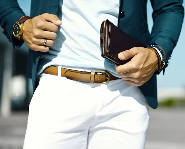 Retrato da moda do homem jovem modelo bonito de empresário em pano casual terno com acessórios nas mãos Foto gratuita