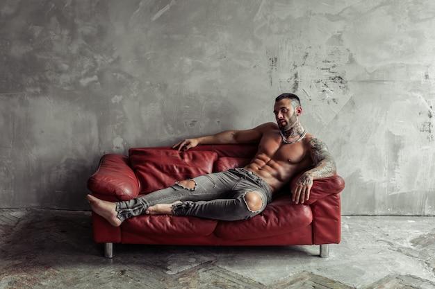 Retrato da moda do modelo masculino nu sexy com tatuagem e barba negra, deitado em pose quente no sofá de couro vermelho. interior de quarto loft com muro de concreto cinza. Foto Premium