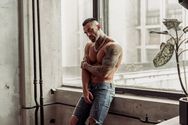 Retrato da moda do modelo masculino nu sexy com tatuagem e uma barba preta em pé em pose quente perto da janela. interior de quarto loft com muro de concreto cinza. Foto Premium