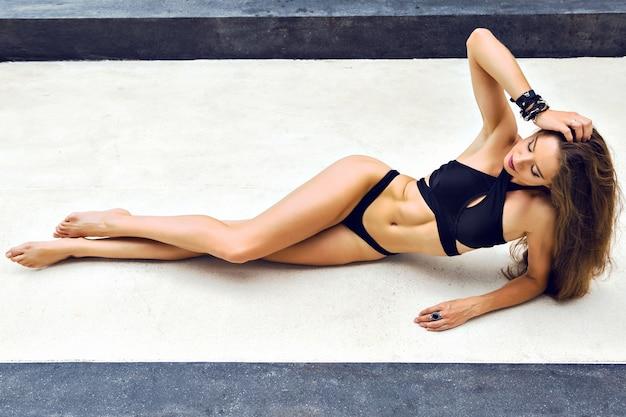 Retrato da moda do verão de uma mulher deslumbrante com corpo esguio e esportivo bronzeado Foto gratuita