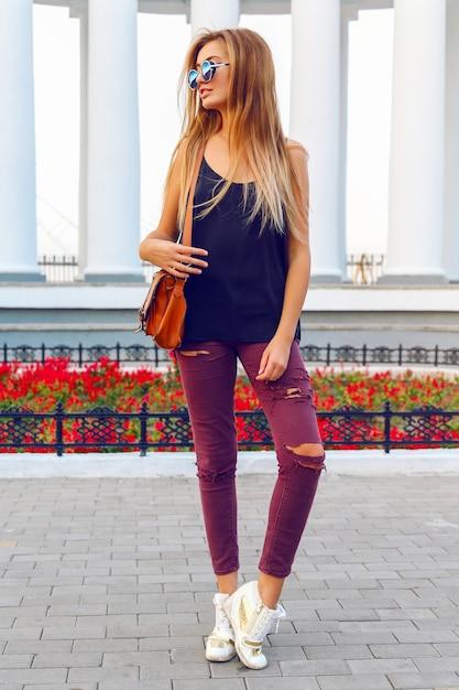 Retrato da moda estilo de rua da jovem mulher sexy em jeans malucos de tênis de salto alto, ter cabelos loiros ombre na moda. Foto gratuita