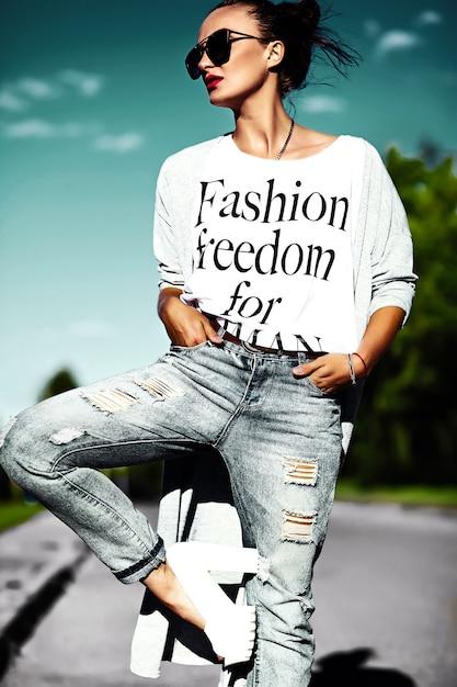 Retrato da moda modelo de glamour elegante engraçado mulher jovem louca bonita com lábios vermelhos no verão brilhante colorido hipster jeans roupas em óculos de sol Foto gratuita