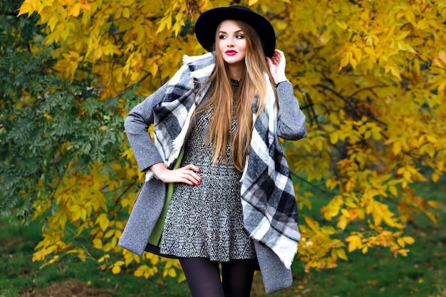 Retrato da moda outono do glamour elegante mulher posando no incrível parque da cidade, casaco elegante, mochila e chapéu vintage. caminhando sozinho, frio Foto gratuita