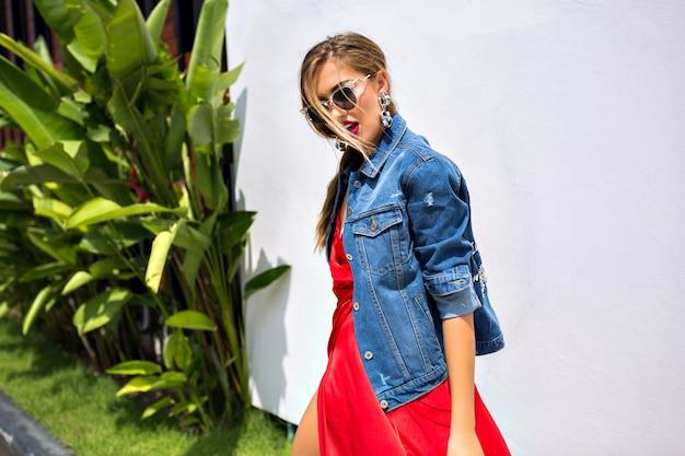 Retrato da moda verão a deslumbrante garota da moda elegante posando do lado de fora em um país tropical, usando um vestido de luxo elegante e jaqueta jeans da moda, dançando e se divertindo. Foto gratuita