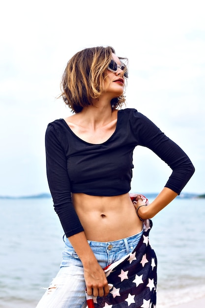 Retrato da moda verão de deslumbrante ajuste sexy mulher, vestindo jeans e top crop, segurando a bandeira americana, passar um tempo na praia em dia chuvoso. Foto gratuita
