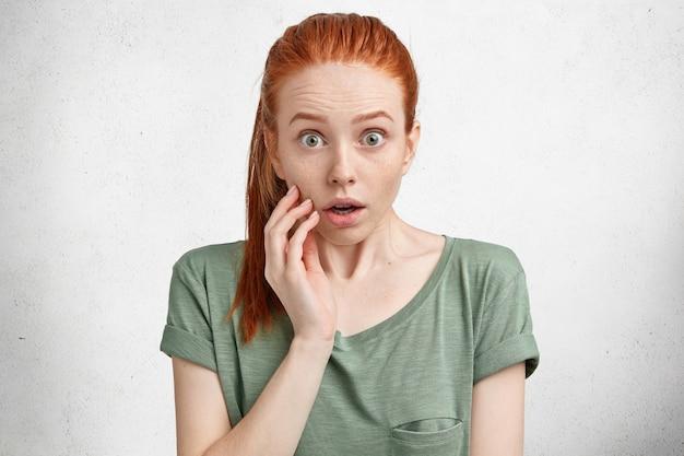 Retrato da modelo feminina de cabelos vermelhos maravilhados com expressão de surpresa, o encara com olhar assustado ao perceber que esqueceu de pagar as contas, sem medo de alguma coisa Foto gratuita