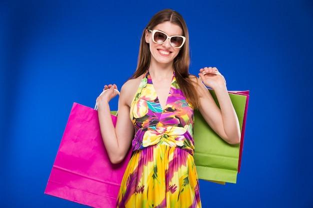 Retrato da morena em óculos de sol com pacotes Foto Premium