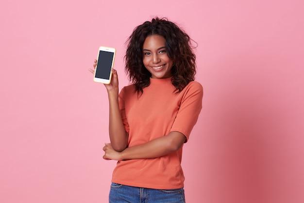 Retrato da mulher africana nova feliz que mostra no telefone móvel de tela em branco isolado sobre o rosa. Foto Premium