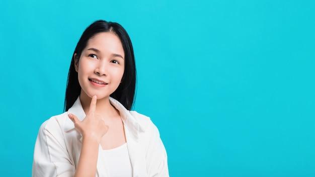 Retrato da mulher asiática bonita segura que pensa e que sorri isolado no fundo azul da cor. Foto Premium