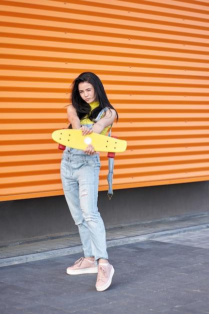 Retrato da mulher atrativa nova positiva que veste a parte superior e a calças de ganga amarelas com skate amarelo. Foto Premium