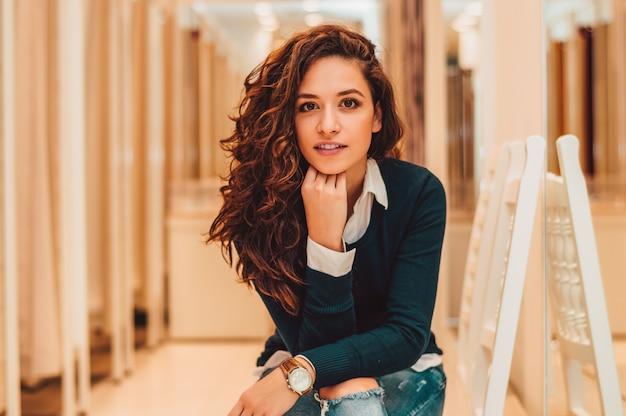 Retrato da mulher bonita que senta-se no vestuario. Foto Premium