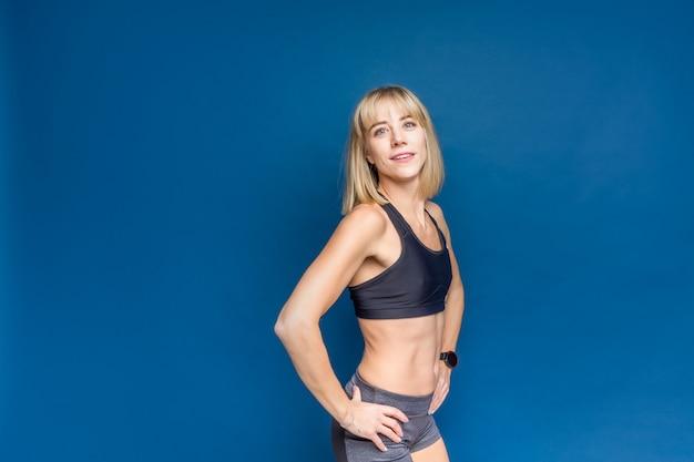 Retrato da mulher caucasiano atlética bonita no sutiã e no short do esporte em um espaço azul do estúdio. copyspace Foto Premium