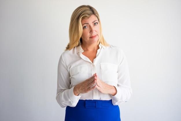 Retrato da mulher caucasiano madura séria na blusa branca que une os dedos. Foto Premium