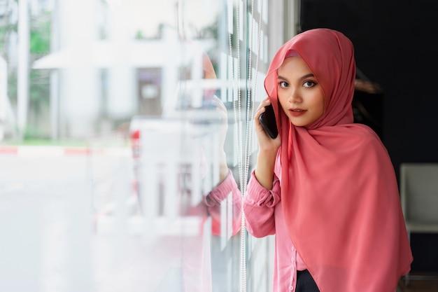 Retrato da mulher de negócio muçulmana nova segura que veste o hijab cor-de-rosa no espaço do trabalho em equipe. Foto Premium