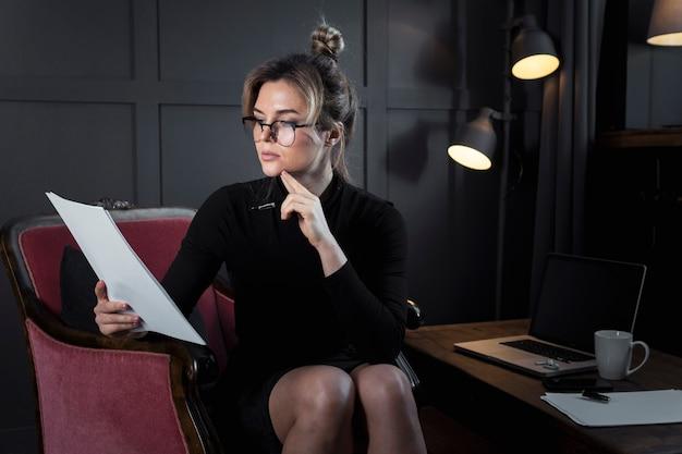 Retrato da mulher de negócios segura que verifica papéis Foto gratuita