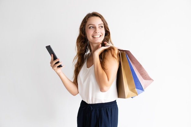 Retrato da mulher de sorriso com sacos de compras e smartphone. Foto gratuita