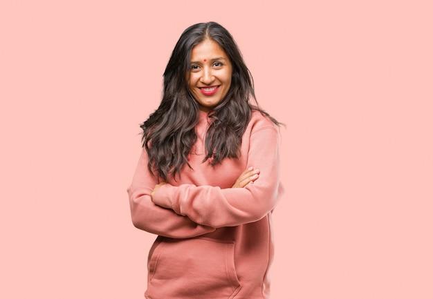 Retrato da mulher indiana nova da aptidão que cruza seus braços, sorrindo e felizes, sendo confiáveis e amigáveis Foto Premium