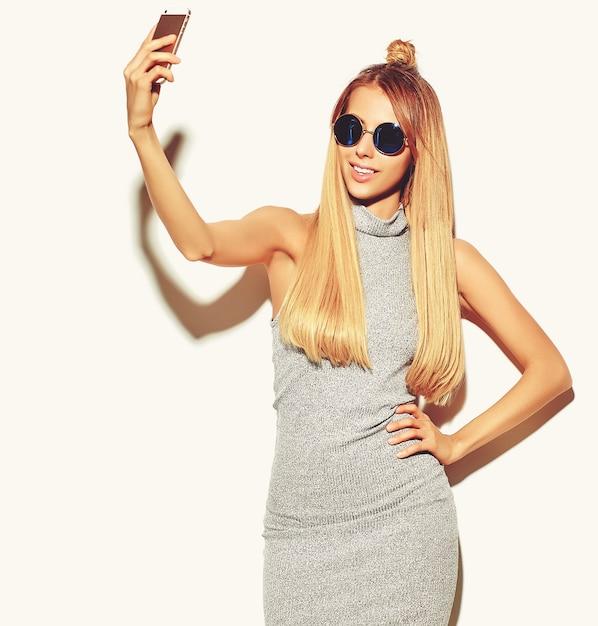 Retrato da mulher loira bonita sorridente feliz bonita em roupas de verão casual hipster cinza sem maquiagem isolada no branco tomando uma selfie Foto gratuita