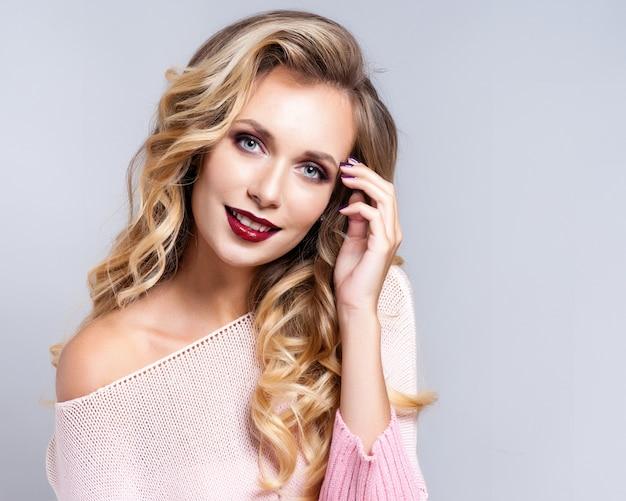 Retrato da mulher loura bonita com penteado encaracolado e composição brilhante. Foto Premium