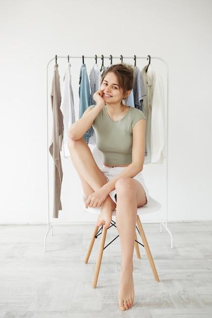 Retrato da mulher moreno nova que sorri sentado na cadeira sobre o vestuário do gancho e a parede branca. Foto gratuita