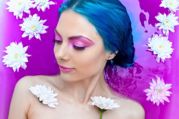 Retrato da mulher nova da forma com o cabelo azul que relaxa na banheira. Foto Premium
