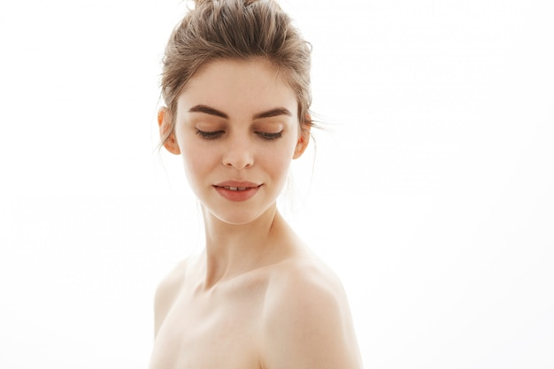 Retrato da mulher nu macia bonita nova com o bolo que olha para baixo sobre o fundo branco. Foto gratuita