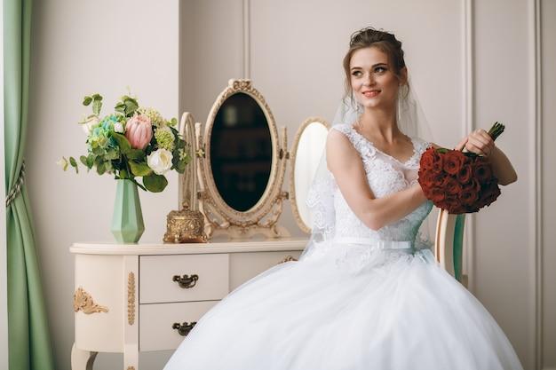 Retrato da noiva bonita no roupão de seda branco com penteado encaracolado e véu longo, sentado perto da janela no quarto, copie o espaço. Foto Premium