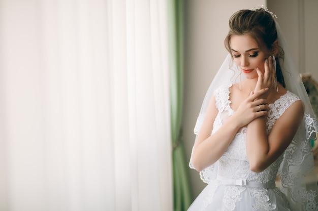 Retrato da noiva linda em roupão de seda branco com penteado encaracolado e véu longo em pé perto da janela no quarto, copie o espaço Foto Premium