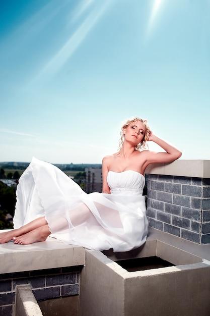 Retrato da noiva modelo loira sexy moda linda garota feminina posando em vestido branco voador no telhado com maquiagem e penteado. céu azul. sol Foto gratuita