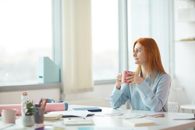 Retrato da vista lateral de uma jovem sardenta sonhando acordada em um escritório moderno enquanto bebe café no local de trabalho, copie o espaço Foto Premium