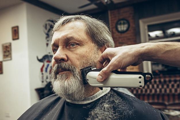 Retrato da vista lateral do close-up do homem caucasiano barbudo sênior considerável que obtém a barba que prepara na barbearia moderna. Foto gratuita