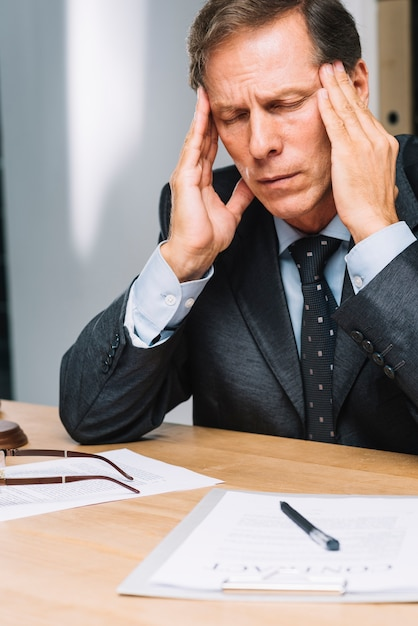 Retrato de advogado maduro estressado, tocando a cabeça no escritório Foto gratuita