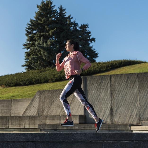 Retrato de ajuste mulher correndo ao ar livre Foto gratuita