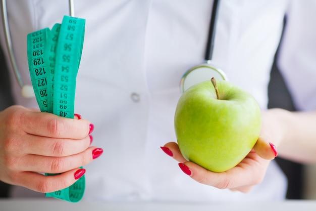Retrato, de, alegre, doutor, nutricionista, medindo, maçã verde, em, dela, escritório Foto Premium