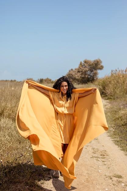 Retrato, de, alegre, mulher, com, pano amarelo, em, natureza Foto gratuita