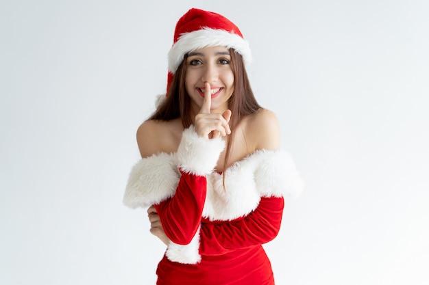 Retrato, de, alegre, mulher, em, santa, equipamento, com, dedo, ligado, lábios Foto gratuita