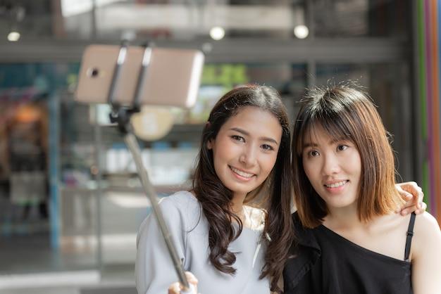 Retrato de alegres duas namoradas sorridentes fazendo um selfie em shopping center. Foto Premium