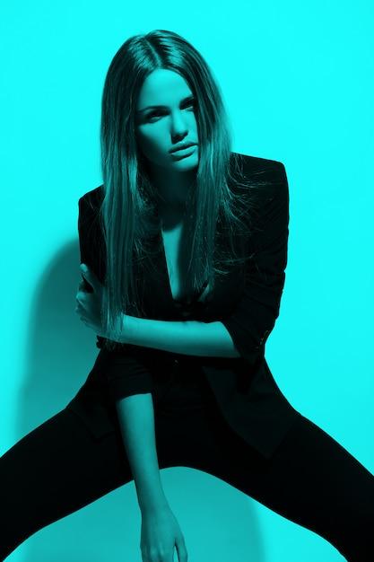Retrato de alta moda look.glamor do modelo sexy elegante caucasiano mulher jovem e bonita em roupas pretas, posando perto da parede Foto gratuita