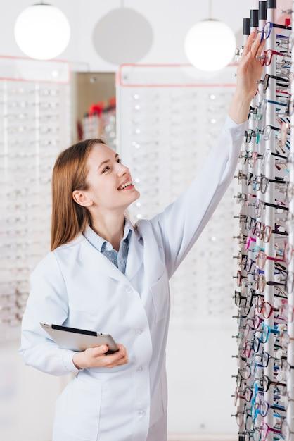 Retrato, de, amigável, femininas, optometrist, com, tabuleta Foto gratuita