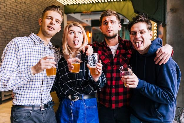 Retrato, de, amigos, segurar, a, copos cerveja Foto gratuita