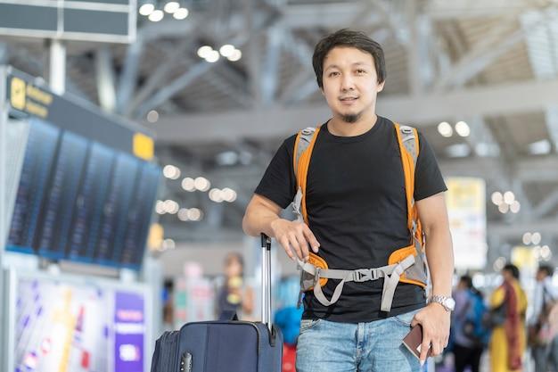 Retrato, de, asiático, viajante, com, bagagem, com, passaporte, ficar, sobre, a, vôo, tábua, para, c Foto Premium
