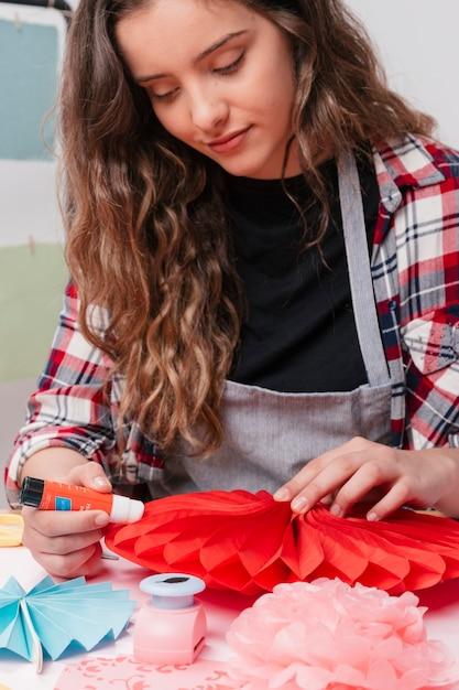 Retrato, de, atraente, femininas, artista, furar, vermelho, origami, flor Foto gratuita