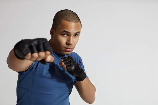 Retrato de atraente jovem mestiço do sexo masculino com cabeça raspada, exercitando-se no ginásio, em pé na parede branca, com o punho erguido na direção da câmera, dando um soco. conceito de boxe, kickboxing e artes marciais Foto gratuita