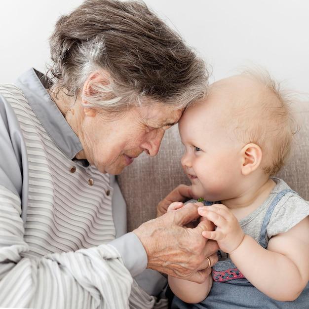 Retrato de avó abraçando brincando com bebê Foto gratuita