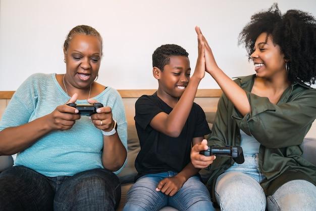 Retrato de avó afro-americana, mãe e filho jogando videogame juntos em casa. conceito de tecnologia e estilo de vida. Foto gratuita