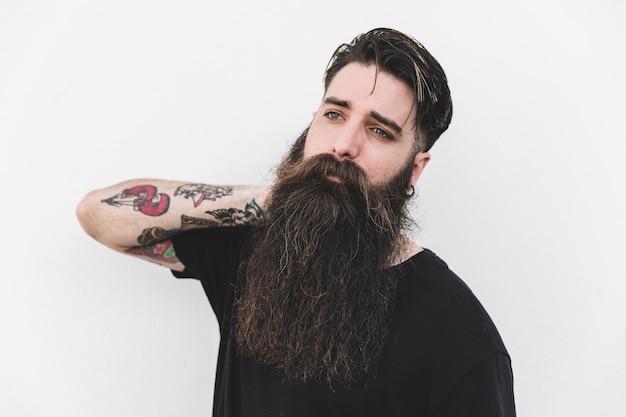 Retrato, de, barbudo, homem jovem, com, tatuagem, ligado, seu, mão, olhando, contra, branca, fundo Foto gratuita