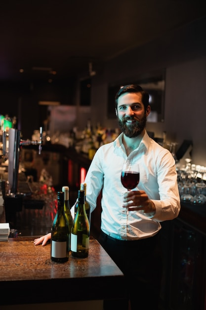 Retrato, de, barman, segurando, copo vinho tinto Foto gratuita