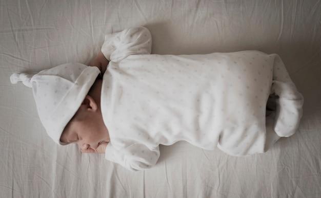 Retrato de bebê dormindo em lençóis brancos Foto gratuita