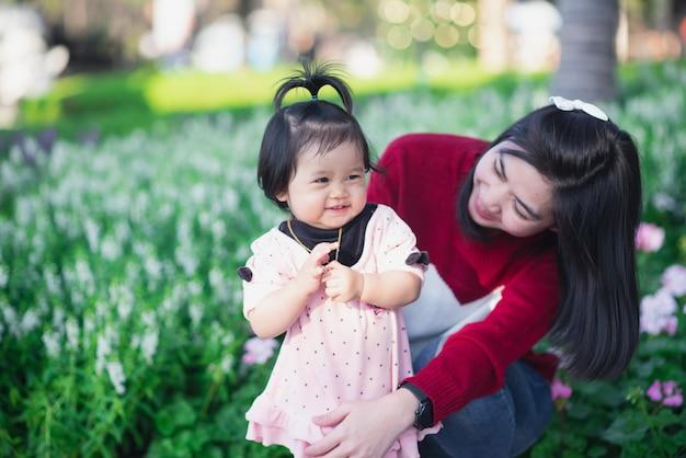 Retrato de bebê fofo e a mãe dela viajam no jardim de flores Foto Premium